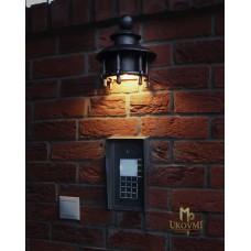 A wrought iron light above a door bell (LB-65)